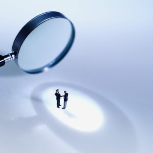 Close-up of magnifying glass focusing on two people